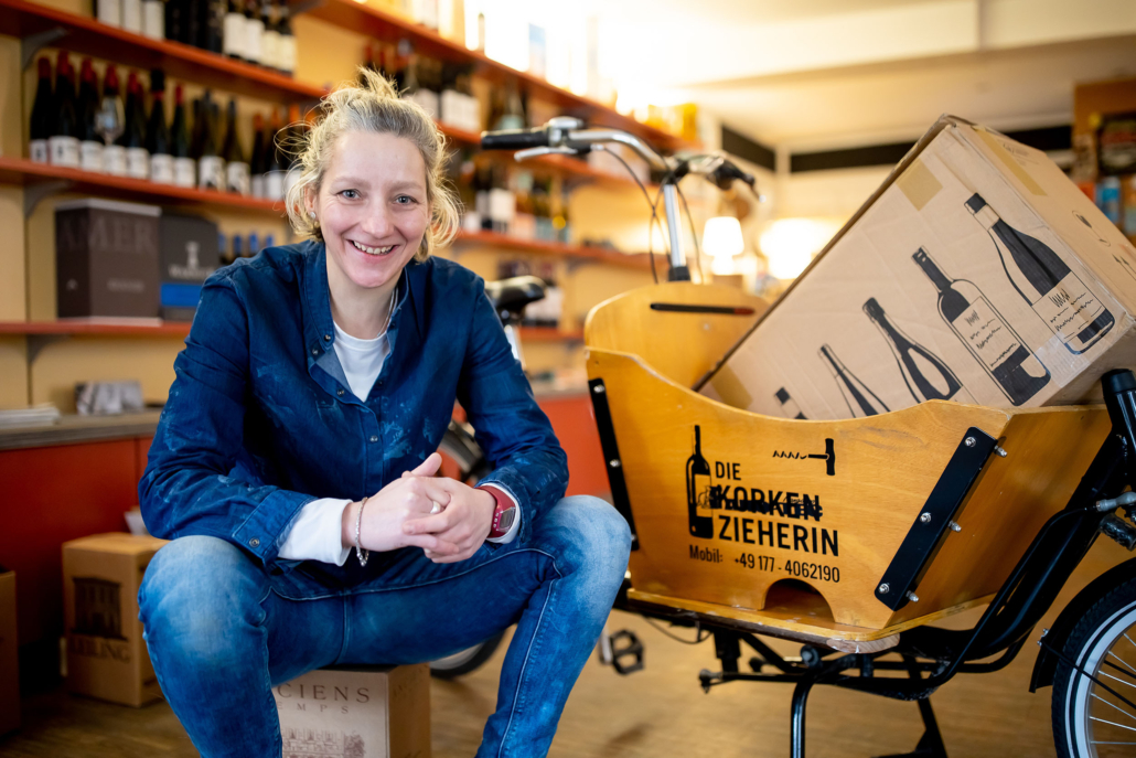 Portraitbild der Korkenzieherin Ornett Ragoschat mit dem Lastenfahrrad im Weingeschäft